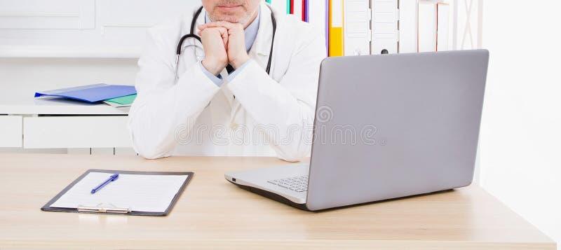 Retrato del doctor mayor en oficina m?dica Hombre en uniforme del blanco imagenes de archivo