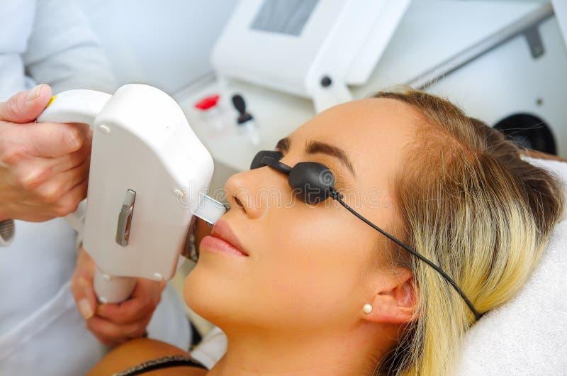 Retrato del doctor que usa un retiro del pelo del laser sobre un bigote de la mujer, en un fondo borroso fotos de archivo libres de regalías