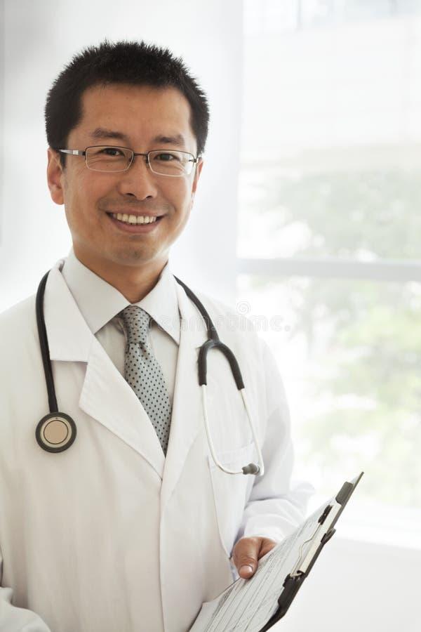 Retrato del doctor sonriente con un estetoscopio y una carta médica foto de archivo