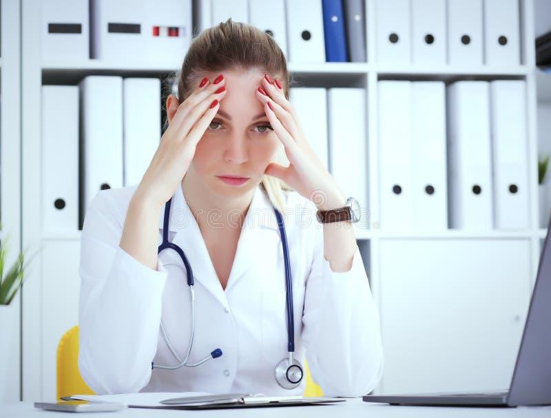Retrato del doctor tensado que se sienta en el lugar de trabajo en el hospital con la mano en la frente en hospital fotos de archivo libres de regalías