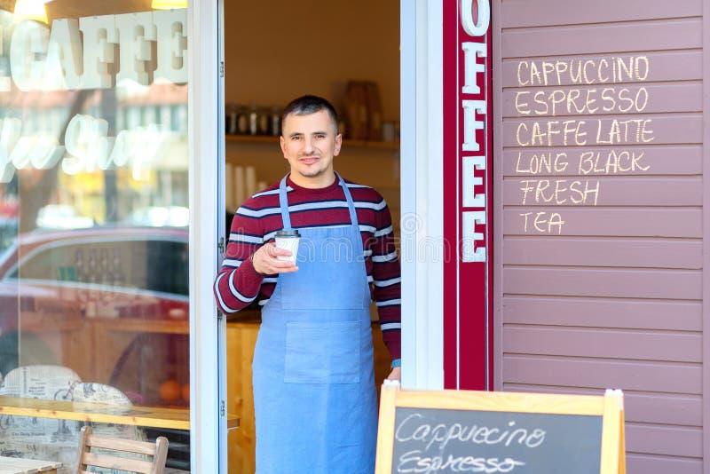 Retrato del dueño de cafetería de la pequeña empresa que sonríe y que se coloca delante de la tienda que sirve un café para lleva fotografía de archivo libre de regalías