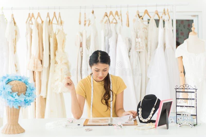 Retrato del dueño de tienda asiático del vestido de boda de la mujer, de la modista de sexo femenino hermosa en tienda y de la pe imagenes de archivo