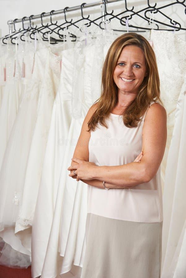 Retrato del dueño de tienda nupcial de sexo femenino con los vestidos de boda imagenes de archivo