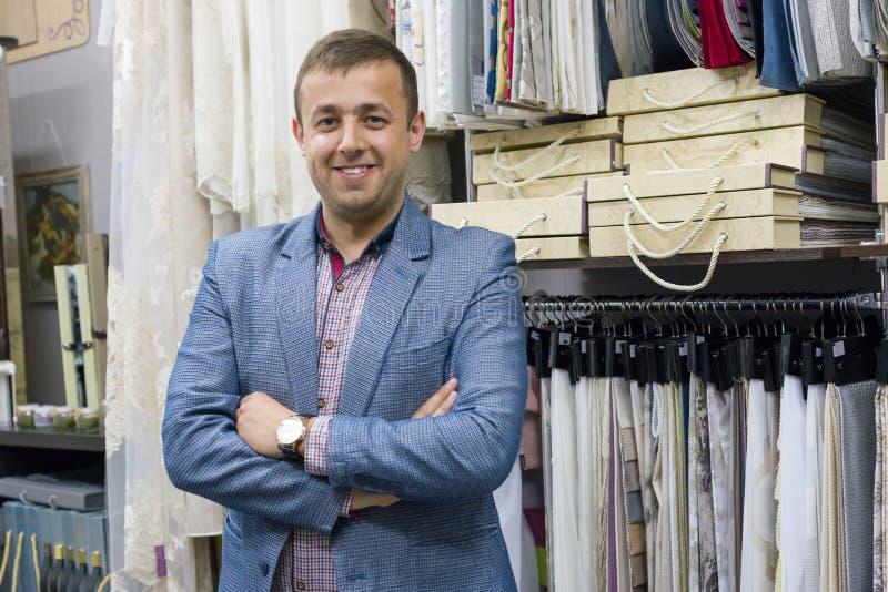 Retrato del dueño feliz del hombre de negocios con los brazos cruzados en tienda interior de las telas, muestras de la tela del f imagenes de archivo