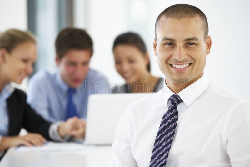 Retrato del ejecutivo de sexo masculino con la reunión de la oficina en fondo fotos de archivo libres de regalías