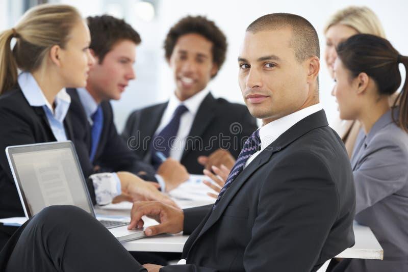 Retrato del ejecutivo de sexo masculino con la reunión de la oficina en fondo imagenes de archivo