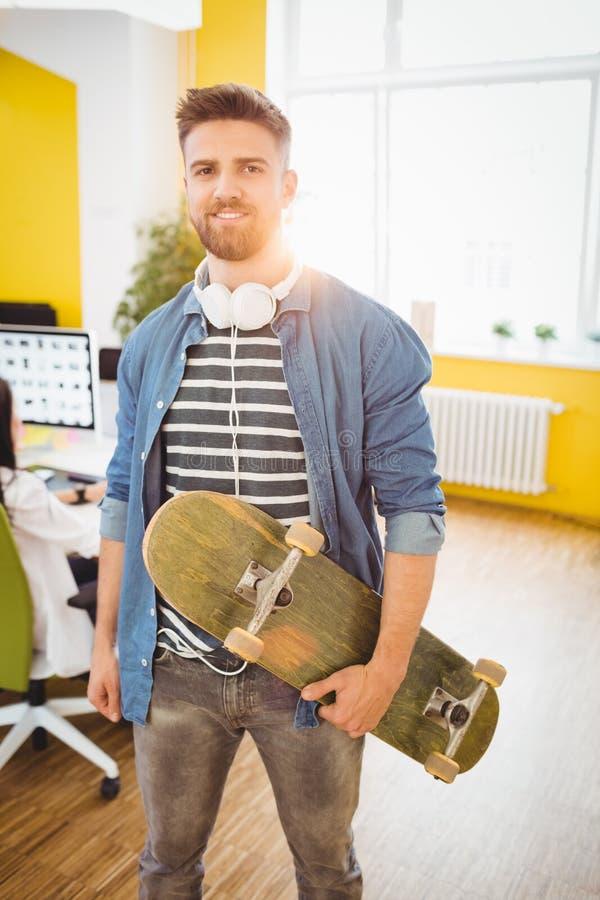 Retrato del ejecutivo hermoso con el monopatín en la oficina creativa imagen de archivo libre de regalías