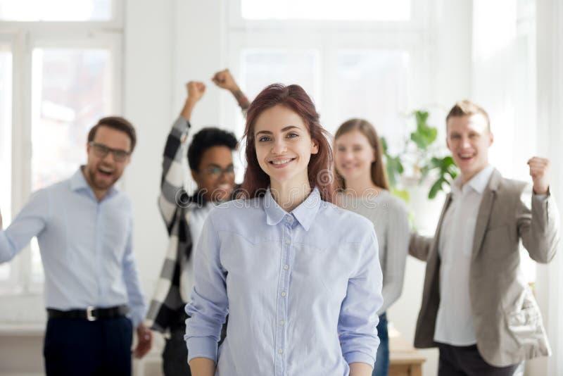 Retrato del empleado de sexo femenino acertado con los colegas emocionados a foto de archivo libre de regalías