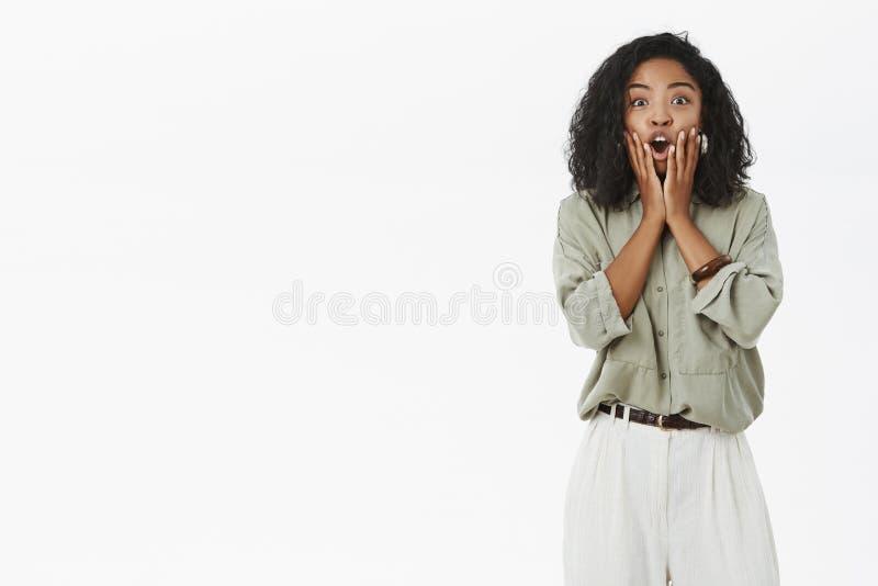 Retrato del empleado de sexo femenino de piel morena impresionado emotivo que reacciona en las noticias asombrosamente impresiona imagenes de archivo