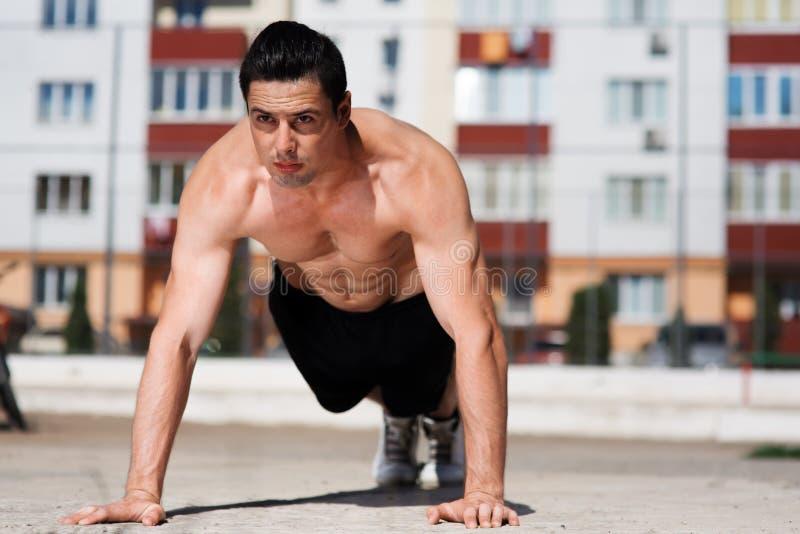 Retrato del empuje-uping joven fuerte del atleta al aire libre en el patio fotografía de archivo libre de regalías