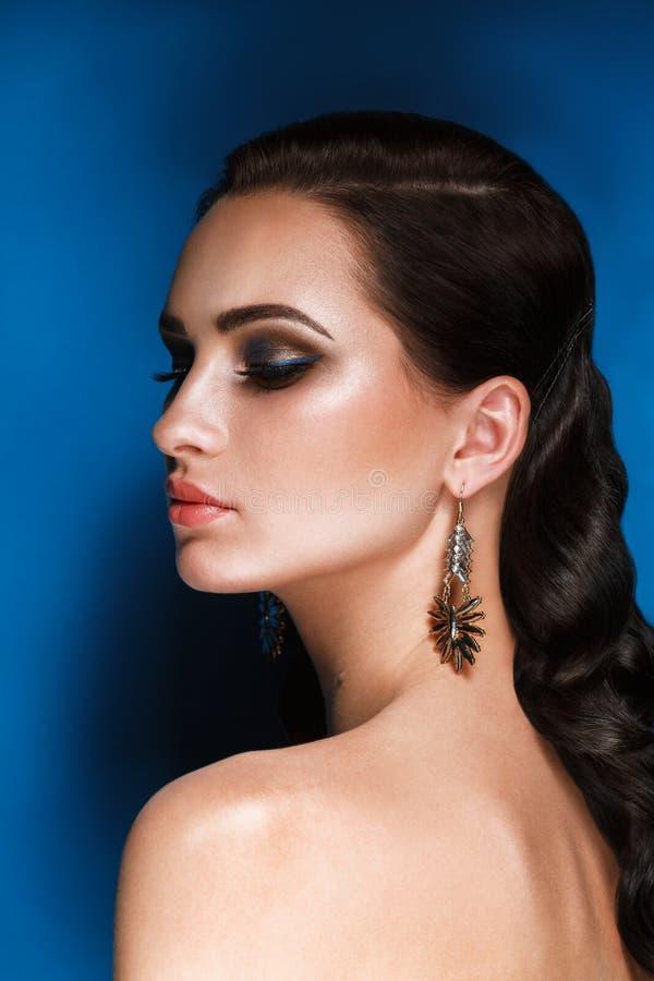 Retrato del encanto del modelo moreno hermoso de la mujer con maquillaje de la tarde y del peinado de Hollywood en el fondo azul fotografía de archivo libre de regalías