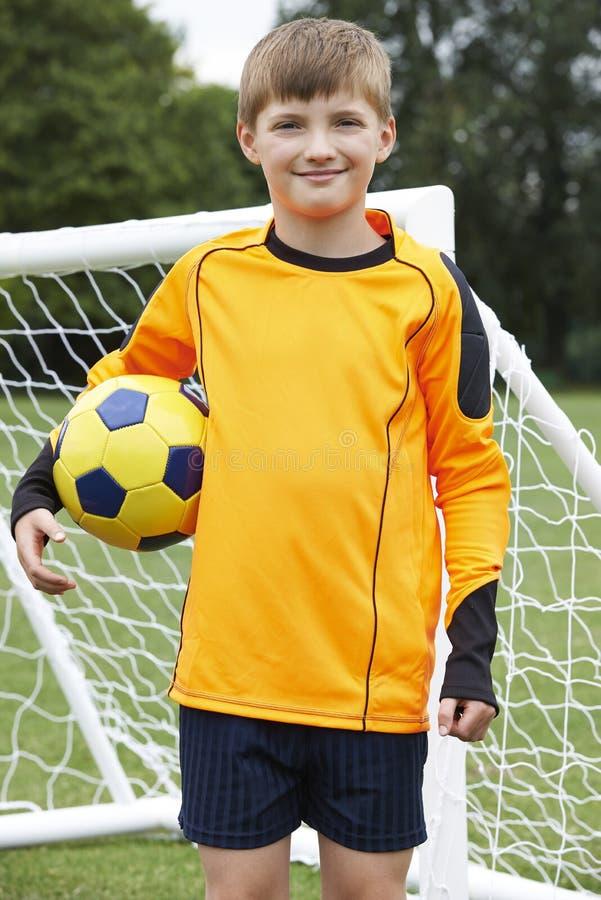 Retrato del encargado de la meta que sostiene la bola en echada del fútbol de la escuela imágenes de archivo libres de regalías