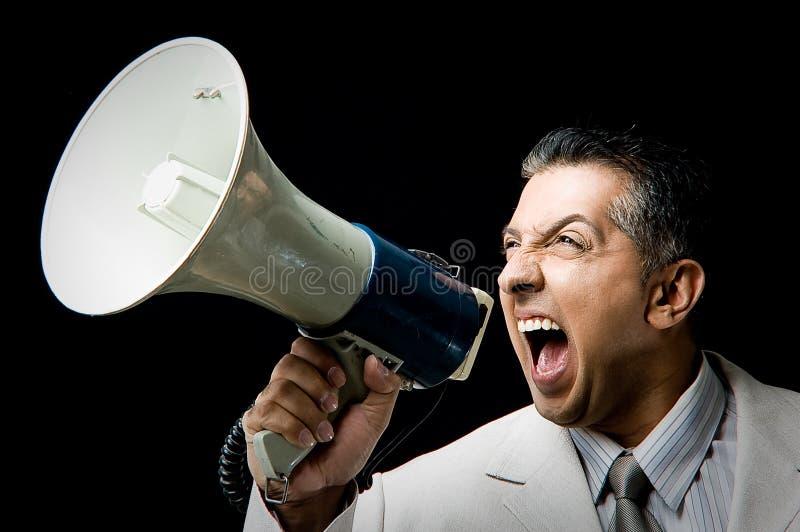 Retrato del encargado que grita en altavoz ruidoso imagenes de archivo