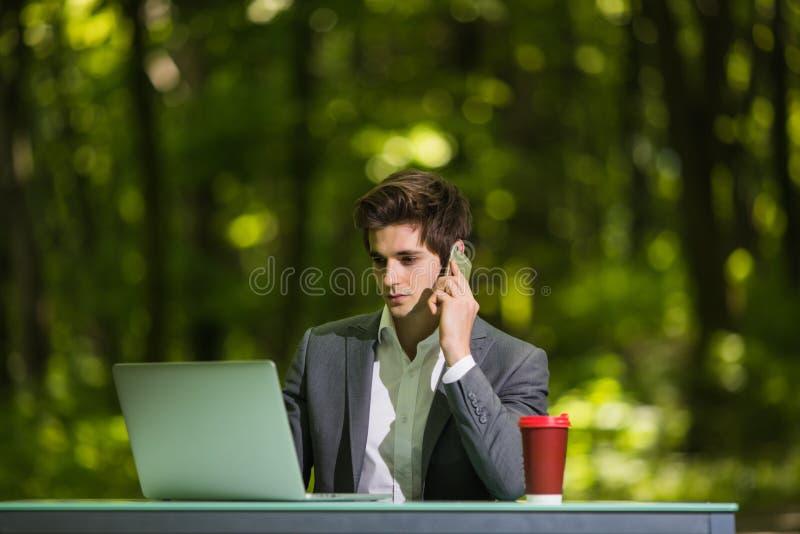 Retrato del encargado que se sienta en el trabajo de escritorio de oficina en el ordenador portátil y la taza de café que hablan  imagenes de archivo