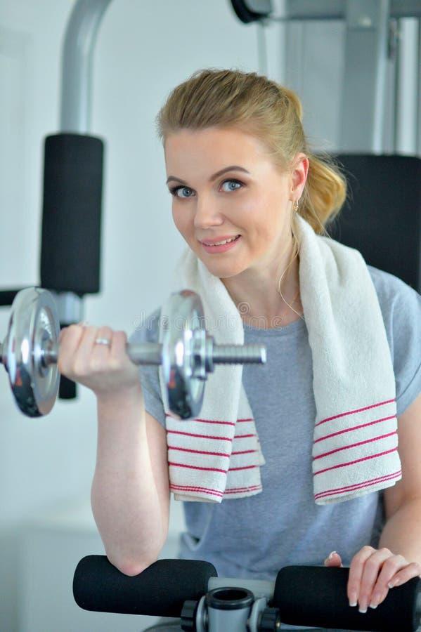 Retrato del entrenamiento deportivo de la mujer joven con pesa de gimnasia en gimnasio imágenes de archivo libres de regalías
