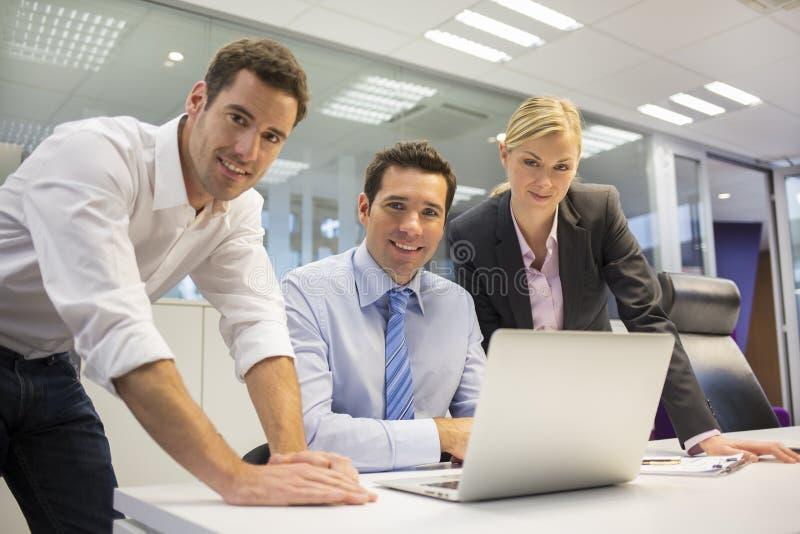 Retrato del equipo alegre del negocio en oficina, mirando la cámara fotos de archivo