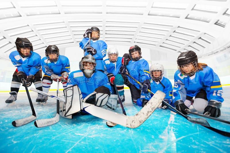 Retrato del equipo de hockey del ` s de los niños en la arena del hielo fotografía de archivo libre de regalías
