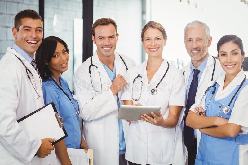 Retrato del equipo médico que se coloca con la tableta y el tablero digitales imagen de archivo libre de regalías