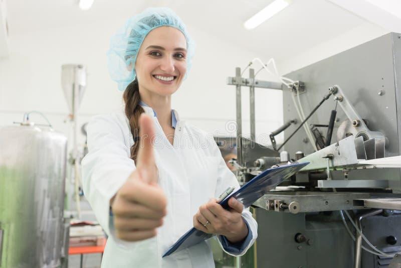 Retrato del especialista feliz de la fabricación de la mujer que muestra los pulgares para arriba fotos de archivo