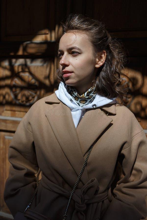 Retrato del estilo de la calle de la mujer joven en capa beige en un día soleado que presenta delante de una puerta de madera del fotografía de archivo libre de regalías