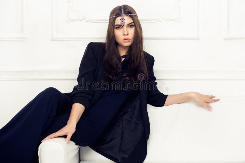 Retrato del estilo de Vogue de la mujer morena hermosa en un sofá fotografía de archivo libre de regalías