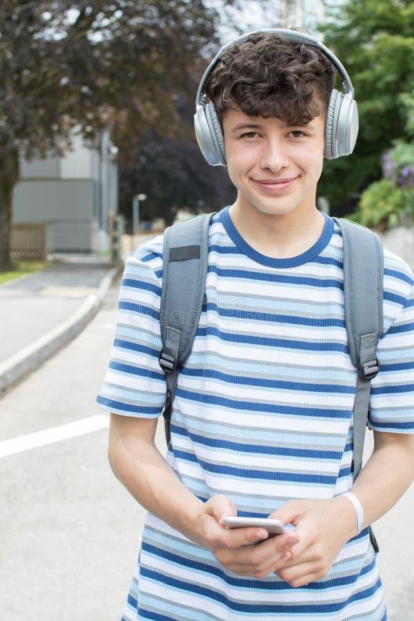 Retrato del estudiante adolescente Outside College Building T que escucha imagenes de archivo