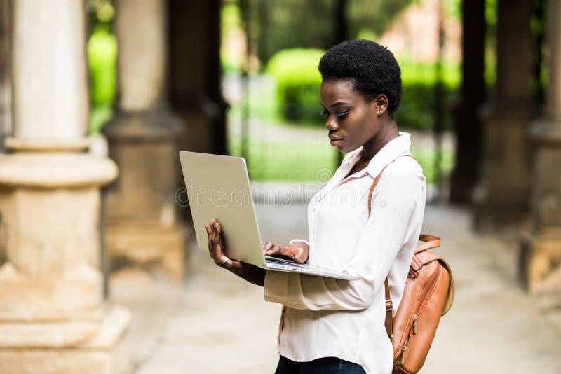 Retrato del estudiante afroamericano sonriente que hace la preparación al aire libre usando el ordenador portátil para la investi foto de archivo