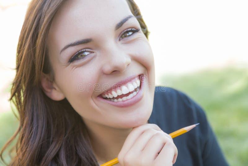 Retrato del estudiante bastante joven con el lápiz en campus fotos de archivo