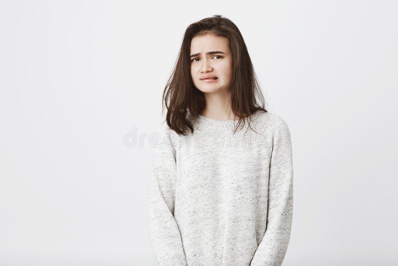 Retrato del estudiante europeo lindo que muestra el desacuerdo y el repugnancia de lo que ella ve, mirando la cámara, sobre foto de archivo