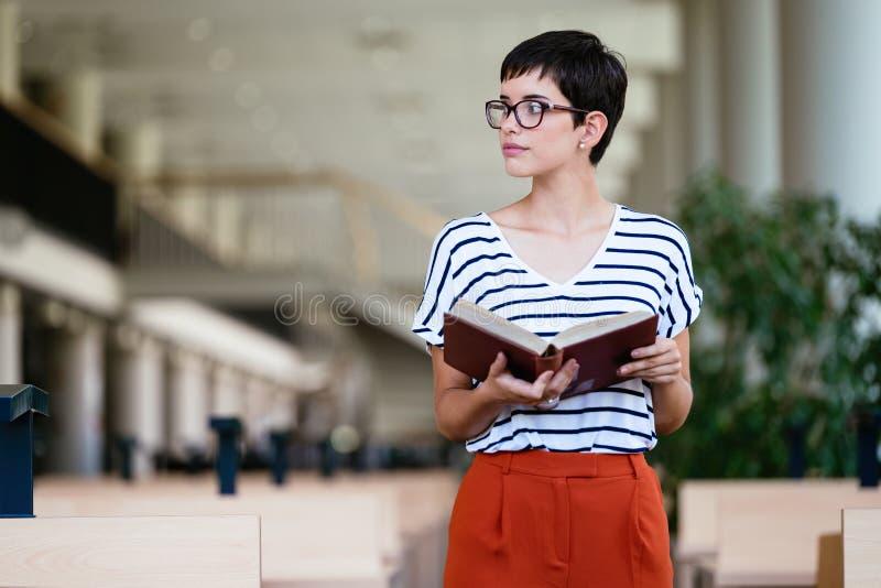 Retrato del estudiante joven en biblioteca imagen de archivo libre de regalías
