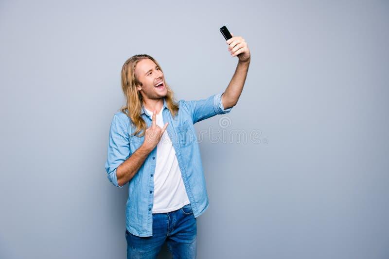 Retrato del estudiante loco que hace el selfie y que gesticula la roca y r imagen de archivo