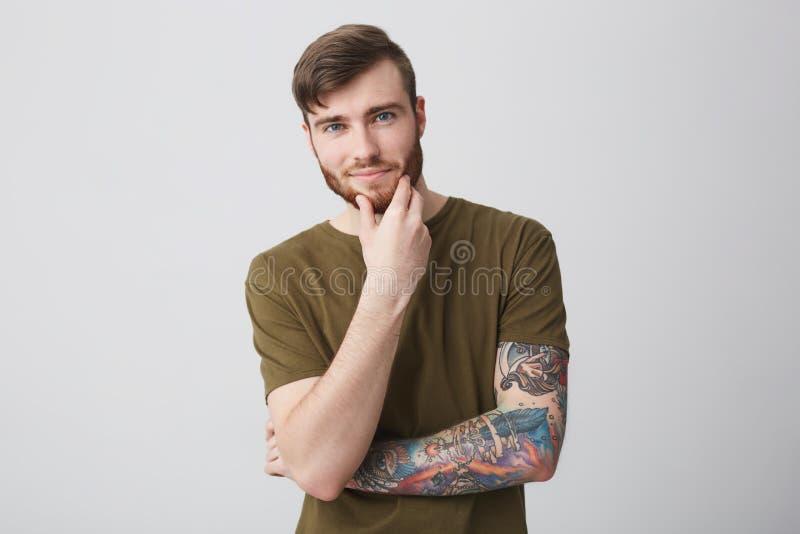 Retrato del estudiante masculino caucásico del jengibre barbudo alegre hermoso con el peinado elegante corto y el brazo tatuado a foto de archivo