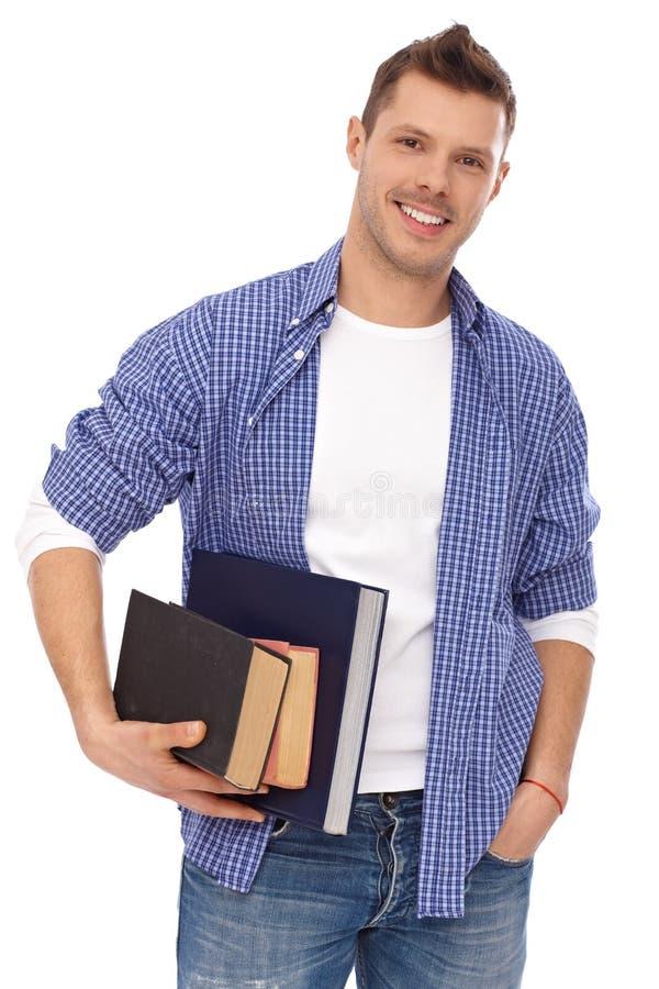 Retrato del estudiante masculino con la sonrisa de los libros imagen de archivo libre de regalías