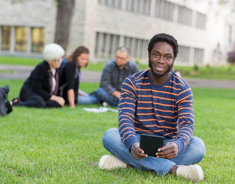 Retrato del estudiante Sitting On Grass en el campus fotos de archivo libres de regalías
