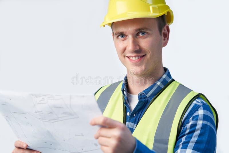 Retrato del estudio del arquitecto Looking At Plans del constructor contra el fondo blanco fotografía de archivo libre de regalías