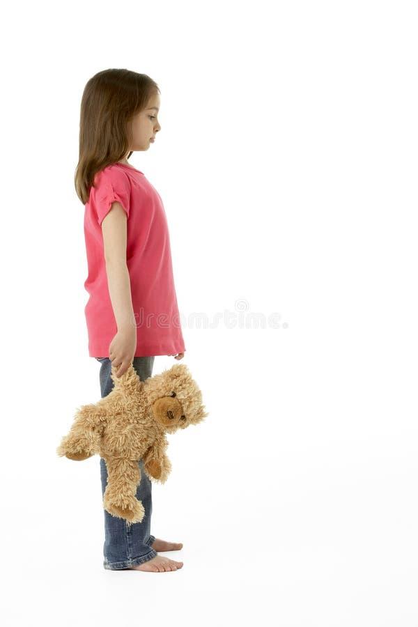 Retrato del estudio de la muchacha que se coloca con el oso del peluche imagen de archivo libre de regalías