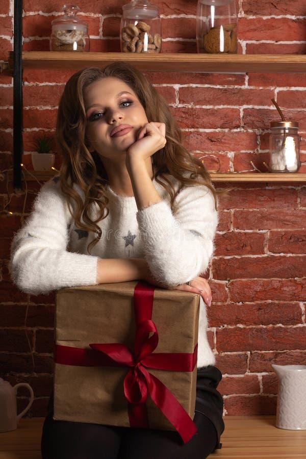 Retrato del estudio de la muchacha rubia adorable que presenta con la caja de regalo en la cocina fotos de archivo