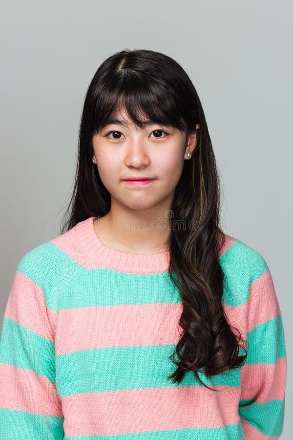 Retrato del estudio de la mujer asiática del este adolescente feliz en fondo gris imagen de archivo