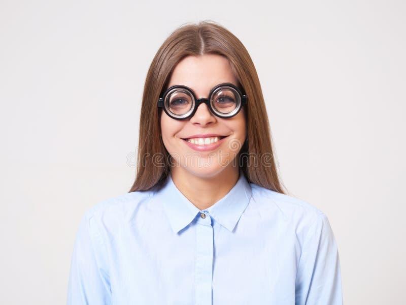Retrato del estudio de la mujer de negocios joven divertida en vidrios del empollón fotografía de archivo