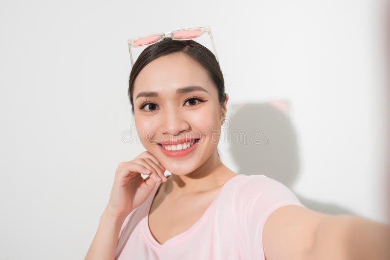 Retrato del estudio de la mujer hermosa que sonr?e con los dientes blancos y que hace el selfie, fotografi?ndose sobre el fondo b imagen de archivo