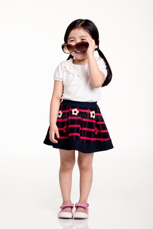 Retrato del estudio de las gafas de sol que llevan y del tener del niño asiático de la muchacha una mirada brillante fotos de archivo