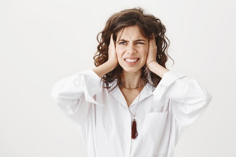 Retrato del estudio de los oídos femeninos caucásicos atractivos insatisfechos enfadados de la cubierta con las manos, mirando a  imágenes de archivo libres de regalías