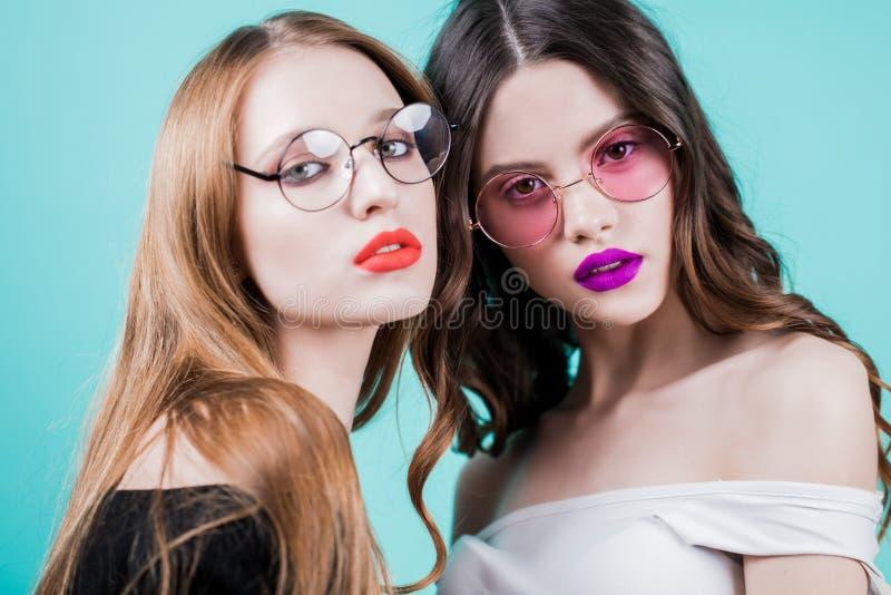 Retrato del estudio de novias Dos mujeres hermosas con maquillaje brillante y vidrios redondos en el fondo azul, cierre para arri foto de archivo