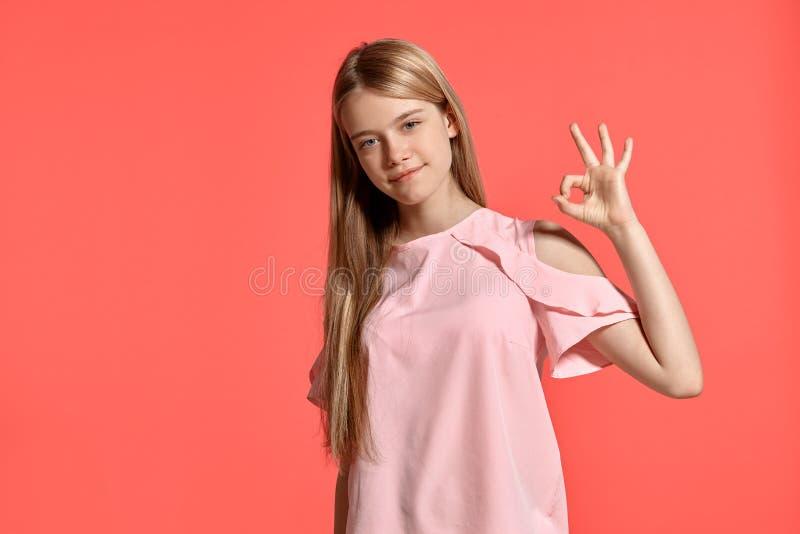 Retrato del estudio de un adolescente rubio de la muchacha hermosa en una camiseta atractiva que presenta en fondo rosado imagen de archivo libre de regalías