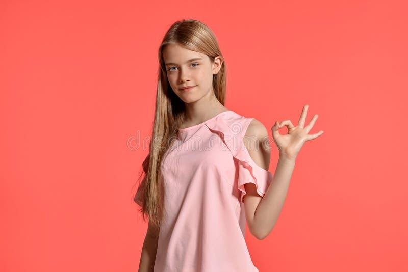 Retrato del estudio de un adolescente rubio de la muchacha hermosa en una camiseta atractiva que presenta en fondo rosado fotografía de archivo libre de regalías