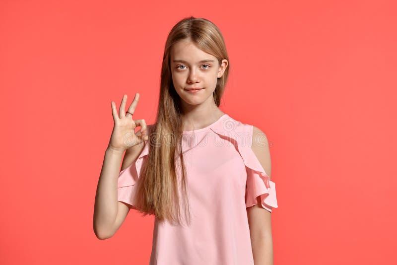 Retrato del estudio de un adolescente rubio de la muchacha hermosa en una camiseta atractiva que presenta en fondo rosado imágenes de archivo libres de regalías