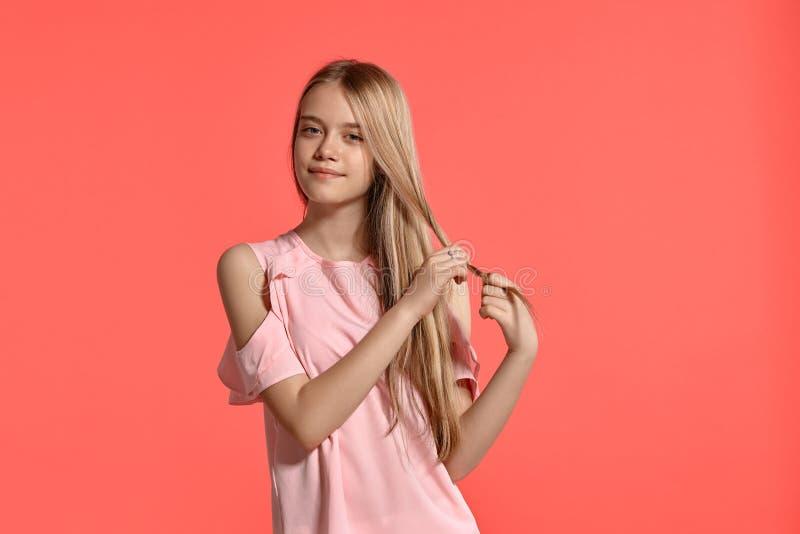 Retrato del estudio de un adolescente rubio de la muchacha hermosa en una camiseta atractiva que presenta en fondo rosado fotos de archivo libres de regalías