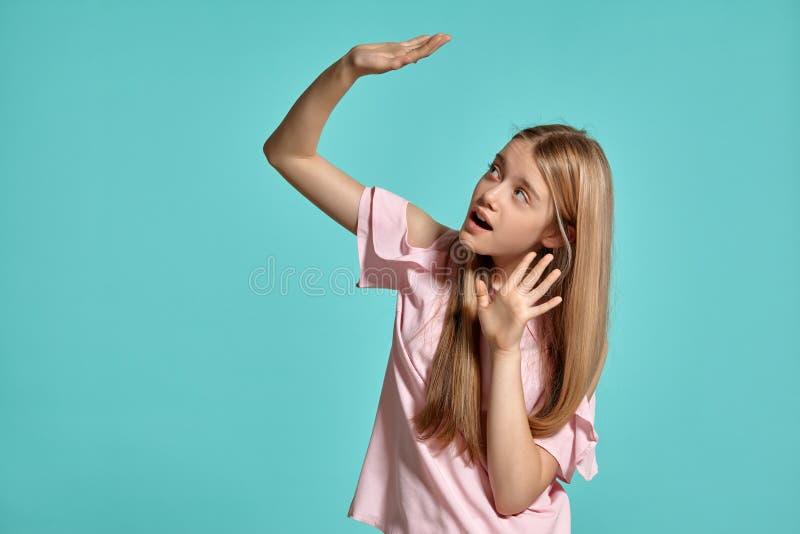 Retrato del estudio de un adolescente rubio de la muchacha hermosa en una camiseta rosada que presenta sobre un fondo azul fotografía de archivo libre de regalías