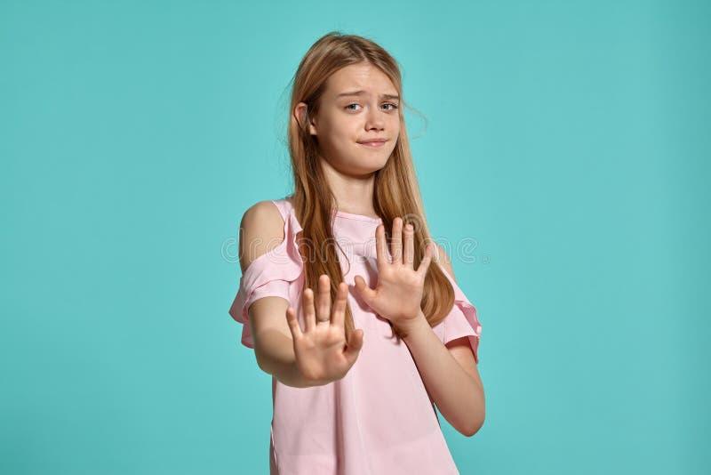 Retrato del estudio de un adolescente rubio de la muchacha hermosa en una camiseta rosada que presenta sobre un fondo azul imagenes de archivo