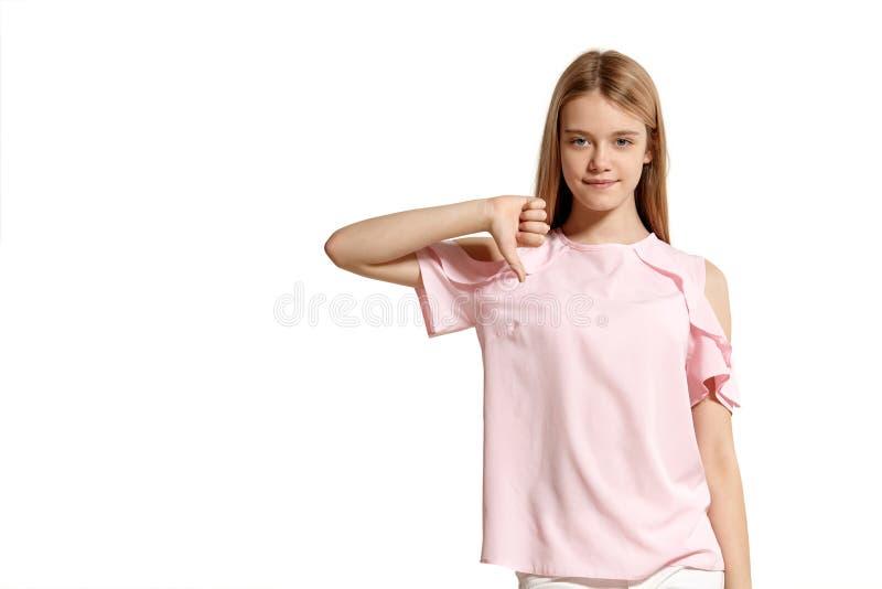 Retrato del estudio de un adolescente rubio de la muchacha hermosa en una presentación rosada de la camiseta aislado en el fondo  imagen de archivo libre de regalías